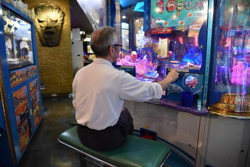 「暇つぶし」と語りながらメダル落としゲームをする男性=東京都豊島区で、筆者撮影