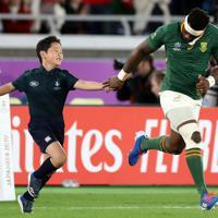 【イングランド-南アフリカ】試合前、南アフリカのコリシ(右)に手を引かれてピッチに入る小野鳳さん=横浜・日産スタジアムで2019年11月2日、喜屋武真之介撮影