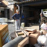 水につかった家財を片付ける狩野忠司さん(左)と妻睦子さん=宮城県石巻市で10月23日