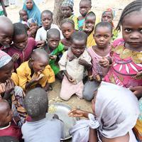 政府非公認の避難民キャンプで、お湯にトウモロコシの粉を入れて作った昼食を食べる子供たち。食材を買うことができず、栄養不足で母乳が出ない女性たちがいる。キャンプでは、肉の代わりに豆を砕いたものを入れるなど工夫し、母親や子供が少しでも栄養を摂れるようにしている=マイドゥグリで2019年9月29日、山崎一輝撮影