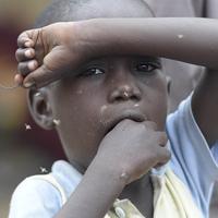 政府非公認の避難民キャンプで、顔に群がるハエを払う国内避難民の子供。政府からの様々な支援を受けることができず、生活に困窮している=ナイジェリア・ボルノ州マイドゥグリで2019年9月29日、山崎一輝撮影