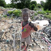 道路脇に積み上げられたゴミ山の中から金属やプラスチックなどを集める子供。集めたゴミをリサイクル業者に売り、収入を得ている。州の所有地で管理が行き届いておらず、次々とゴミが集まり異臭を放っている=マイドゥグリで2019年9月24日、山崎一輝撮影