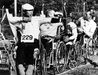 1964 Tokyo Paralympics -- A Japanese dartchery athlete, left, competes on his way to taking the bronze medal in the sport.
