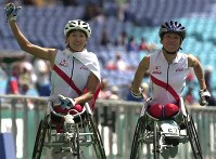 2000 Sydney Paralympics -- Japan's Kazu Hatanaka, left, who took the silver medal in the women's wheelchair marathon, and Wakako Tsuchida, who secured bronze in the event, celebrate with spectators. (Mainichi/Satoru Ishii)