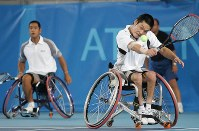 2004 Athens Paralympics -- The Japanese pair of Shingo Kunieda, right, and Satoshi Saida compete on their way to winning the gold medal in the men's wheelchair tennis doubles.