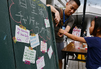 Messages in support of the rebuilding of Shuri Castle are seen on a board set up at a concert venue in Naha, Okinawa Prefecture, on Nov. 3, 2019. (Mainichi/Tadashi Sano)