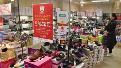 キャッシュレス決済のポイント還元を知らせるポスターを掲示する靴店=福岡市博多区の川端通商店街で2019年10月1日、田鍋公也撮影