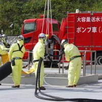 貯水槽の上部にホースを取り付ける訓練参加者たち=静岡県御前崎市の中部電力浜岡原発で