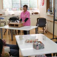利用者の前で木製オルゴールを演奏する杉山さん(中央)