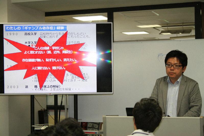 カジノの専門学校の受講生にパチンコ依存症だったころの体験を話す三宅隆之さん(右)。カジノのディーラー志望者にギャンブル依存症患者の心理や行動パターンなどを詳しく伝えている=東京都内で