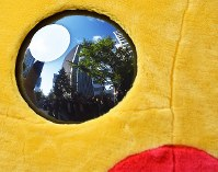 A view of Midosuji Avenue is seen reflected in the eyes of a Pikachu costume during the