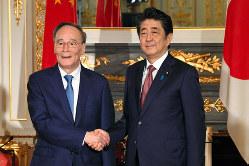 中国の王岐山国家副主席(左)との会談は和やかだったが・・・・・・=東京都港区の迎賓館で10月23日(代表撮影)