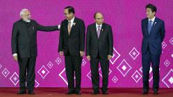 RCEP首脳会議の記念撮影で並ぶインドのモディ首相(左端)と安倍首相(右端)ら各国首脳=タイ・バンコク近郊で11月4日、AP