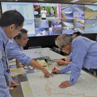 大津波で使えなくなる道路や迂回路を地図で確認する職員ら