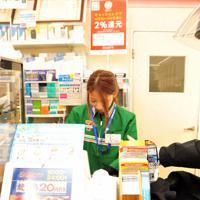 訓練で犯人役(右)に模造刀を突きつけられ、金品を要求される店員=福知山市のセブンイレブン福知山末広店で、佐藤孝治撮影