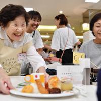 「注文をまちがえるリストランテ」で料理を提供する認知症の女性(左端)=京都市下京区で、猪飼健史撮影
