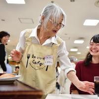 飲み物の提供先を間違える女性スタッフ(中央)。間違えても笑顔があふれる=京都市下京区、猪飼健史撮影