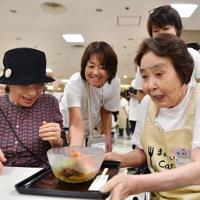 ボランティアと協力して料理を提供する参加者(右端)=京都市下京区で、猪飼健史撮影
