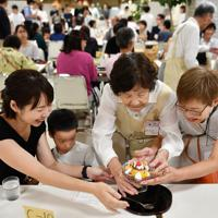 笑顔で協力して料理を受け取る客も大勢=京都市下京区で、猪飼健史撮影
