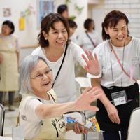 客に手を振る女性スタッフ(手前)とボランティア=京都市下京区で、猪飼健史撮影