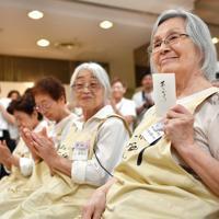 給料を手に笑顔を見せる認知症の参加者=京都市下京区で、猪飼健史撮影