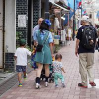 ファンの人たちと一緒に子どもと歩くアイス市場さん=東京都墨田区で、米田堅持撮影