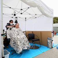 避難所前のテントで髪を切る理容師の若月敦さん(左奥)=長野市で2019年11月7日、佐々木順一撮影