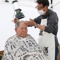 避難所前のテントで髪を切る理容師の若月敦さん(右)=長野市で2019年11月7日、佐々木順一撮影