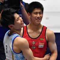 体操男子個人総合で優勝し2位の萱和磨(左)と抱き合う橋本大輝=高崎アリーナで2019年11月8日、宮間俊樹撮影