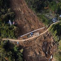 台風19号による土砂崩れで大きくえぐられた山肌。中央の道路沿いに行方不明となっている佐々木睦さん、定子さん夫婦の自宅跡があり、その下では2人の捜索が続く=相模原市緑区牧野で2019年11月8日、本社ヘリから北山夏帆撮影
