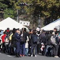 「祝賀御列の儀」を沿道で観覧するため、手荷物検査を受ける人たち=東京都千代田区で2019年11月10日午後0時35分、尾籠章裕撮影