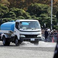 天皇陛下の即位を披露する「祝賀御列の儀」を前にコース上に水をまく散水車=東京都千代田区で2019年11月10日午後0時49分、幾島健太郎撮影