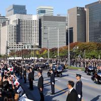丸の内や大手町のビル群を背に進む祝賀御列の儀のパレード=東京都千代田区で2019年11月10日午後3時14分、山本晋撮影