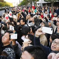 青山通りを通過する「祝賀御列の儀」の車列にスマートフォンのカメラを向ける人たち=東京都港区赤坂8丁目で2019年11月10日午後3時24分、石井諭撮影