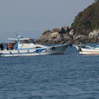 海上ボーリング調査の予定海域で9日午後、作業船(左)に準備作業に入らないように呼び掛ける反対派の船