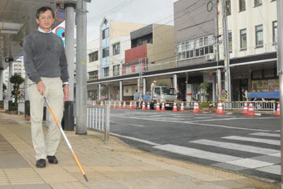 商店街を歩きながら白杖で路面を調べる福留史朗さん。点字ブロックとタイルが同じ黄色で判別しにくい=鳥取市栄町で