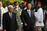 China's President Xi Jinping, right, and his Greek counterpart Prokopis Pavlopoulos, left, inspect the guard of honor by Evzones, the Greek Presidential guards, outside the Presidential palace in Athens, on Nov. 11, 2019. (AP Photos/Thanassis Stavrakis)