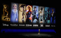 In this April 3, 2019, file photo characters from Disney and Fox movies are displayed behind Cathleen Taff, president of distribution, franchise management, business and audience insight for Walt Disney Studios during the Walt Disney Studios Motion Pictures presentation at CinemaCon 2019, the official convention of the National Association of Theatre Owners (NATO) at Caesars Palace in Las Vegas. (Photo by Chris Pizzello/Invision/AP)