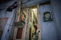 In this Nov. 10, 2019 photo, Lorenzo Ballester poses at the door of his house, decorated with a photo of revolutionary hero Ernesto