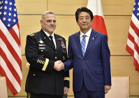 Japan's Prime Minister Shinzo Abe, right, shakes hands with U.S. Chairman of the Joint Chiefs of Staff Gen. Mark Milley prior to their talks at the prime minister's office in Tokyo, on Nov. 12, 2019. (Kazuhiro Nogi/Pool Photo via AP)