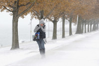 A woman walking the half mile from Chicago's Adler Planetarium to the Chicago Aquarium braces herself in the stiff wind and blowing snow off Lake Michigan, on Nov. 11, 2019, in Chicago. (AP Photo/Charles Rex Arbogast)