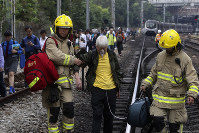Firefighters help an elderly woman as commuters walk on the railway after their train service is disrupted by pro-democracy protesters in Hong Kong, on Nov. 12, 2019. (AP Photo)