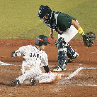 Ukyo Shuto slides home to score on Sosuke Genda's bunt and tie the game during Japan's 3-2 win over Australia in their WBSC Premier 12 game. (Kyodo)