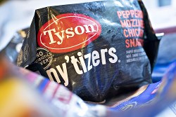 Tyson Foods Inc. Products As Profit Boosted Amid Rising Beef Demand Signage is arranged on a Tyson Foods Inc. Tyson any'tizers brand pepperoni mozzarella chicken snackers package in an arranged photograph in Tiskilwa, Illinois, U.S., on Monday, Aug. 6, 2018. The largest U.S. meat company posted better-than-expected fiscal third-quarter earnings as beef demand rose and cattle costs fell, Tyson said Monday in a statement. Photographer: Daniel Acker/Bloomberg