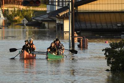 千曲川の堤防が決壊して浸水した住宅街からボートで救助される住民=長野市で