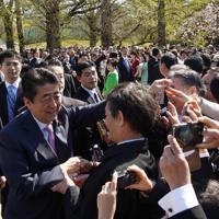 「桜を見る会」の来場者と握手をして回る安倍晋三首相(左)=東京都新宿区の新宿御苑で2019年4月13日、代表撮影
