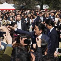 「桜を見る会」の来場者と握手をして回る安倍晋三首相(右)=東京都新宿区の新宿御苑で2019年4月13日、代表撮影