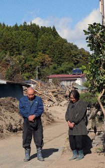 Yoshiji Sato and his wife Kesano observe a moment of silence as a siren sounds, in front of their home in the Miyagi Prefecture town of Marumori, in northeastern Japan, where landslide debris remains. (Mainichi/Naoaki Hasegawa)