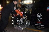 A driver transfers wheelchair user Minekazu Tsuchiya into a universal design taxi in Tokyo's Edogawa Ward on Oct. 30, 2019. (Mainichi/Buntaro Saito)