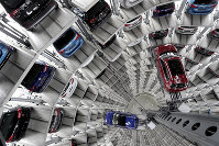 In this March 14, 2017 file photo Volkswagen cars are lifted inside a delivery tower of the company in Wolfsburg, Germany. (AP Photo/Michael Sohn)
